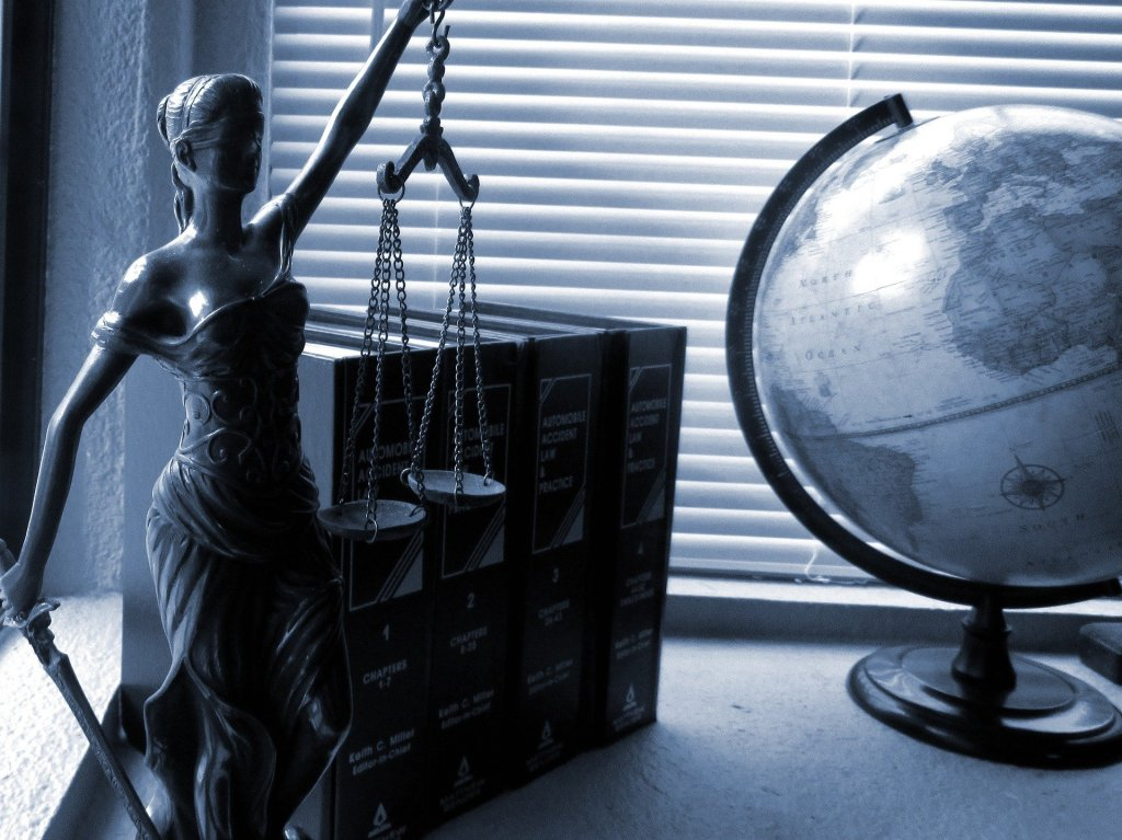 Scales of justice and globe in grayscale